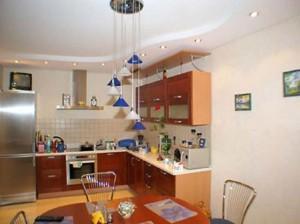 Светлый натяжной потолок делает кухню большей