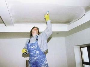 Специалист штукатурит потолок